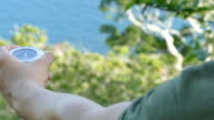 Man's hand holds a small directional compass outdoors to magnetic north video