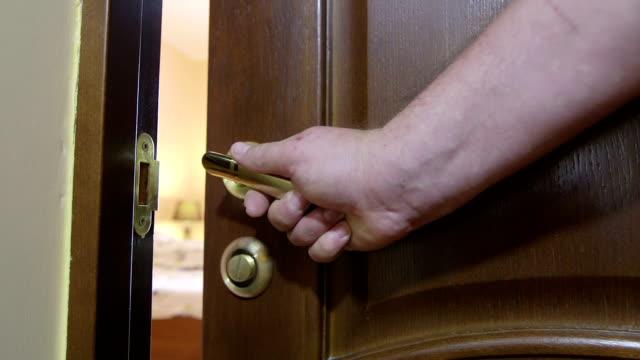Man's hand opening the door to bedroom with unmade bed video