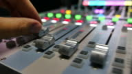 A mans hand pulling up the knobs of an audio mixer in a recording studio video