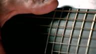 Man's hand touching guitar strings. Music performance. Super slow motion macro video video