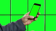 Man's hand with phone on a green background. video