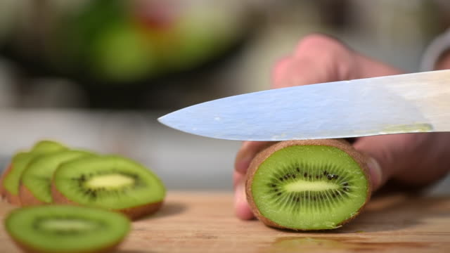 Man's hands cutting kiwi video