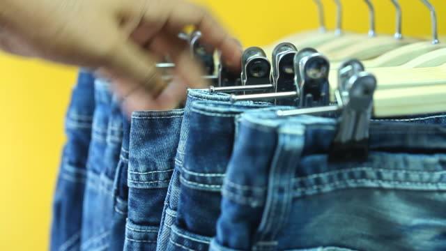 Man's hands looking through jeans rack video