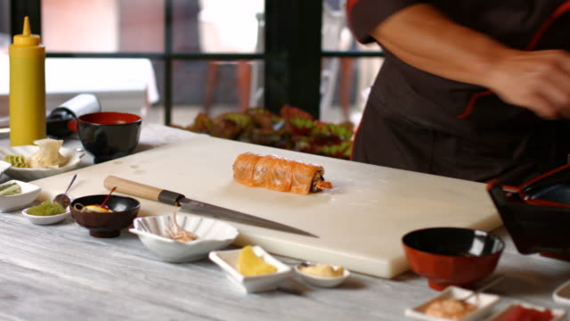Man's hands making sushi rolls. video