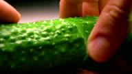 Man's hands splitting green cucumbers on wooden cutting board. FullHD close up shot video
