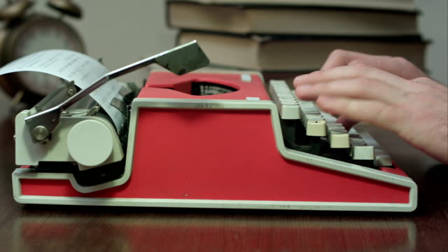 Man's hands typing on a red mechanical typewriter video
