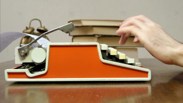 Man's hands typing on a red retro typewriter on a table with books video