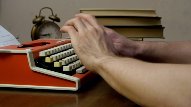 Man's hands typing on a red retro typewriter video