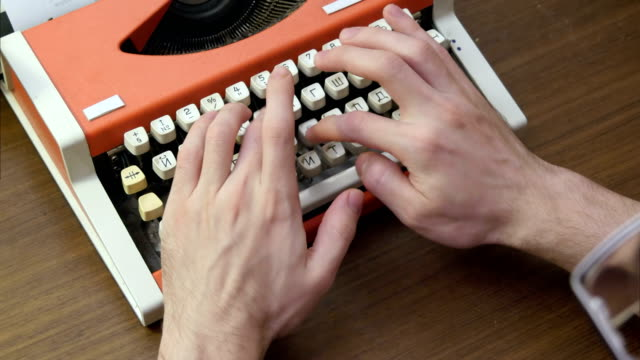 Man's hands typing on an old red mechanical typewriter video