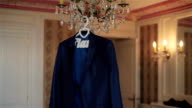 Mans jacket hanging on luster waiting for groom to wear in luxury room interior big day special occasion. Silk fabrics men suit clothing fashion. Henpecked husband male ready for family video