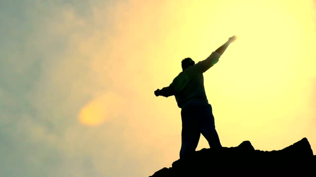 Man's Sylohuette Stretching Arms toward Heaven Colorful Religious Background HD video