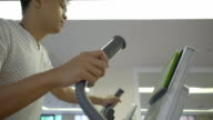 Man's working out on the exercise bike in the modern gym video