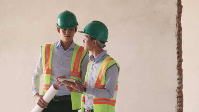Manual worker, engineer and architect with blueprint in construction site video