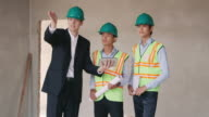 Manual workers and engineer with ipad in construction site video