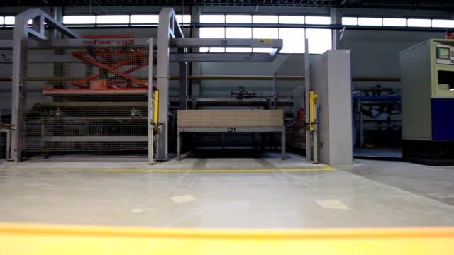 Manufacture of ceramic tiles, yellow truck transports cargo, Industrial interior, close-upIndustrial interior video