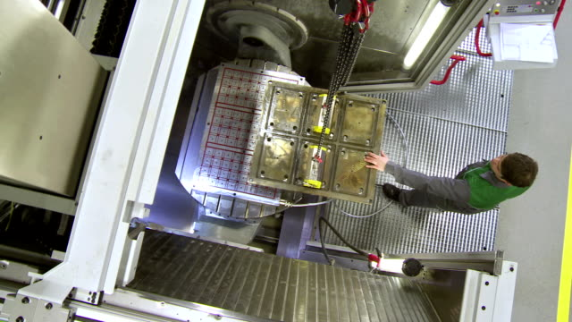 CS Manufacturing Worker Lifting A Machine Mould video