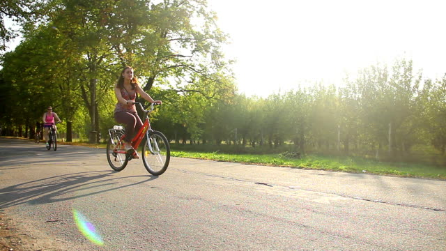 Many adults and children cycling in municipal park, people enjoying video