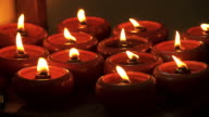 Many candle flames glowing in the dark, create a spiritual atmosphere. video