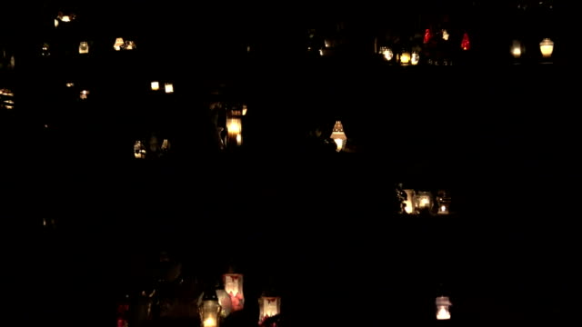 Many candles on cemetery at all saints day at night. Zoom out. FullHD video