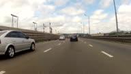 Many cars go across the bridge. video