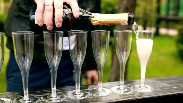Many elegant empty and half-empty wine glasses of wine or champagne on the festive table in wedding day video