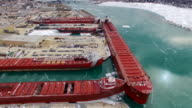 Many large freighter ships docked in ice covered waters video