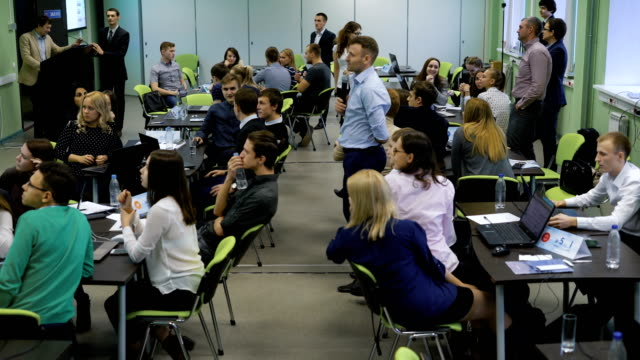 Many people in the room sitting together at the tables and participating in the process of teambuilding. Men and women inside the room are managers of one company and they are involving in interesting business game. Coach standing in the center of the video