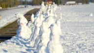 Many snowman on the roadside of the village video