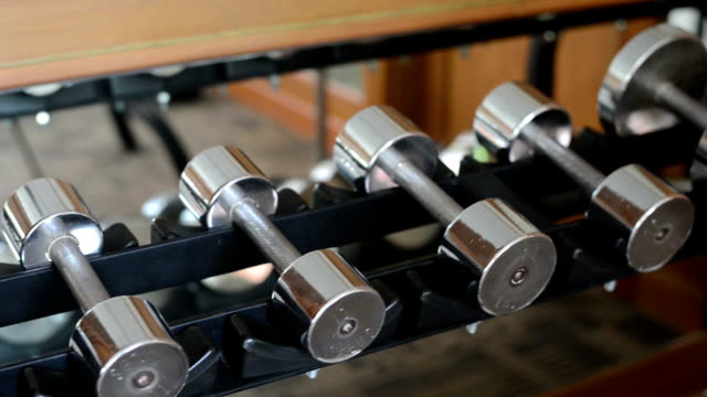 Many sports dumbbells in gym video