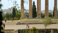 Many tourists go sightseeing around ruins of ancient building, summer vacation video