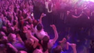 Many young people dancing, enjoying music, filming show on stage during concert video