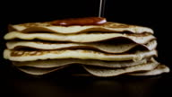 Maple syrup pours out pancakes. Slow motion video
