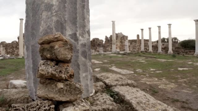 Marble gray column in front of camera on background agora white antique columns ancient town Salamis east Cyprus Famagusta video