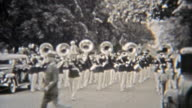 1937: Marching band parading with tuba band horns playing. video