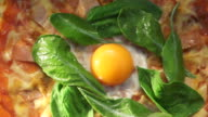 margarita pizza topping with green spinach and raw egg yolk. Italian fusion food video