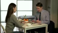 Married people, marriage relationship and modern life, husband and wife at home, man and woman having breakfast. Portrait of happy businessman working with ipad tablet while partner is talking to him video