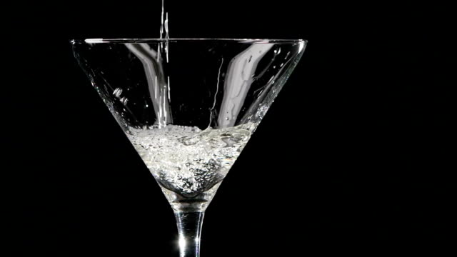 Martini being poured into a glass on black background. Slow video