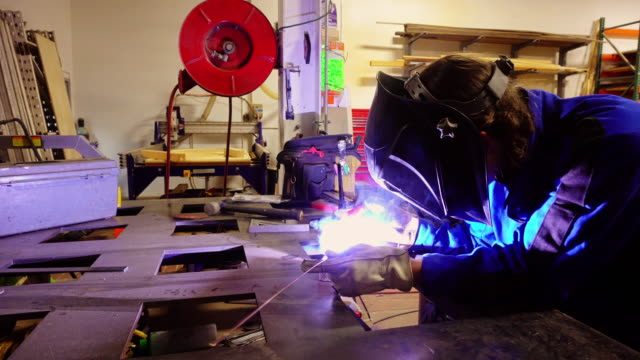 Mask Wearing Metalworker Using Welder in Brightly Lit Workshop video
