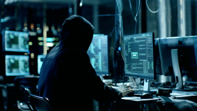 Masked Hacktivist Organizes Massive Data Breach Attack on Corporate Servers. They're in Underground Secret Location Surrounded by Displays and Cables. video