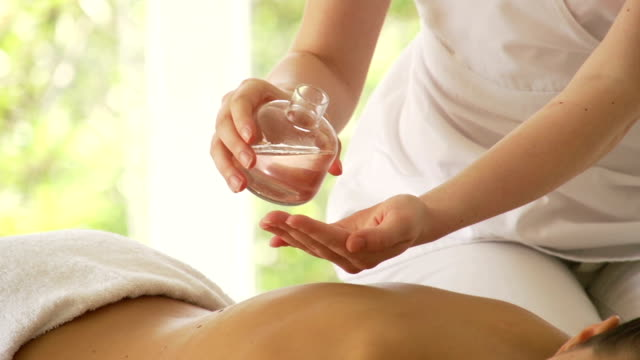 Massage therapiest pouring oil onto hands video