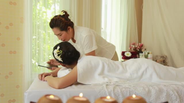 Massage Therapist showing massage menu on the digital tablet video