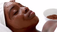 Masseuse applying product on her client face video
