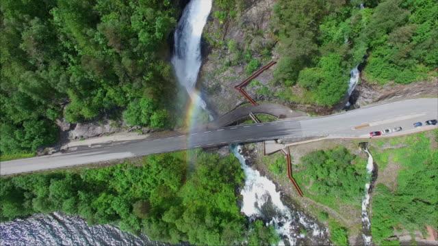 Massive Svandalsfossen waterfall creating rainbow on road bridge in Norway video
