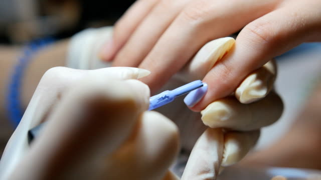 Master in gloves makes a manicure close-up video