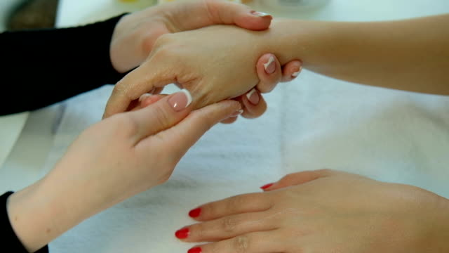 Master of manicure makes cold paraffin therapy for hands of client video