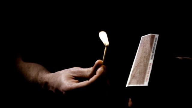 Matchstick lit off of box closeup at night video