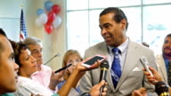 Mature African American politician answers questions after political rally video