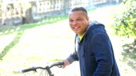 Mature African-American man in park standing with bicycle video