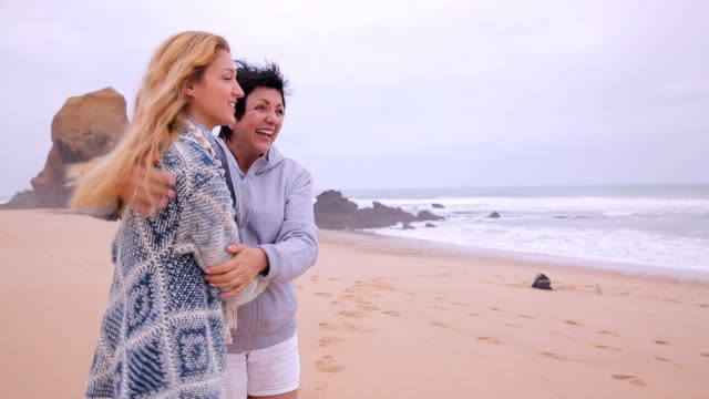 Mature attractive woman and her adult daughter admiring the deserted ocean beach. video