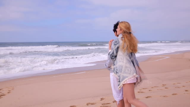 Mature attractive woman and her adult daughter admiring the ocean beach. video